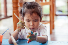 Little girl is painting her hand Stock Image
