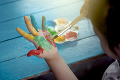 Little girl is painting her hand Stock Photos