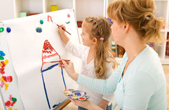 Little girl painting with her mother Stock Images