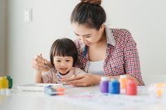 Little girl painting with her mother at home.  Royalty Free Stock Images