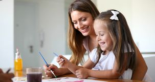 Little girl painting with her mother at home royalty free stock image