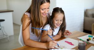 Little girl painting with her mother at home stock images