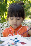 A little girl painting at home garden royalty free stock images