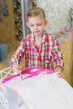 Little girl is painting a house for dolls royalty free stock photos