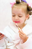 Little girl painting lips Stock Images