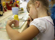 Little girl painting a matrioshka russian doll stock photos
