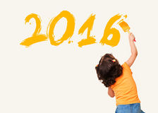 Little girl painting new year 2016 wall background Stock Images