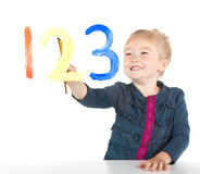 Little girl painting numbers on a window Stock Photos