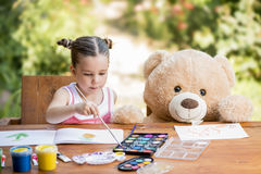 Little girl painting outdoor with her teddy bear friend Stock Photos