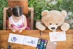 Little girl painting outdoor with her teddy bear friend Stock Images