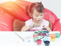 Little Girl Painting with paintbrush and colorful paints by finger hand paint color ,unlimited boundless imagination Royalty Free Stock Image