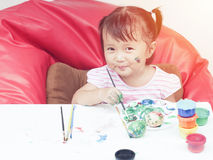 Little Girl Painting with paintbrush and colorful paints by finger hand paint color ,unlimited boundless imagination Stock Images