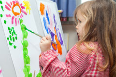 Little girl painting on paper. Cute little blond girl holding brush and painting on paper Stock Photo