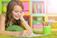 Little girl painting with pencil in her room Royalty Free Stock Image