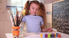 Little girl painting stock footage