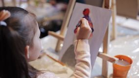 A little girl is painting a picture on canvas. School of Fine Arts. Desktop easel and acrylic paints. A little girl is painting a picture on a canvas on an easel stock footage