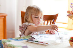 Little girl painting picture with watercolor stock photography
