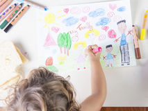 Little girl painting a pink dress of a girl in a kids drawing of Royalty Free Stock Images