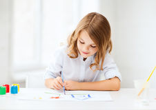 Little girl painting at school Stock Images