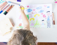Little girl painting a sun in a kids drawing of multi-racial Fam Stock Images