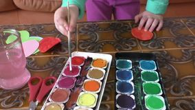 Little girl painting watercolors with her hands stock footage
