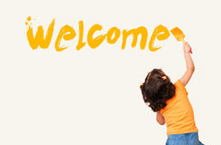 Little girl painting Welcome on wall background Stock Photography