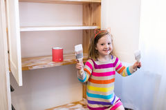 Little girl painting wooden closet. Happy preschool age girl holding a brush painting a wooden bedroom closet with white color paint. Child learning furniture stock images