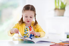 Little girl painting and writing Stock Photography