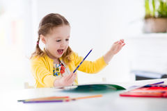 Little girl painting and writing Royalty Free Stock Photography