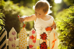Little girl paints fence. Little cute girl paints fence on summer Royalty Free Stock Photo