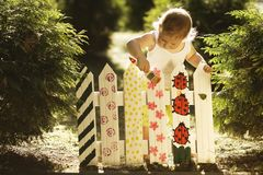 Little girl paints fence. Little cute girl paints fence on summer Royalty Free Stock Photography