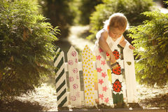 Little girl paints fence. Little cute girl paints fence on summer Stock Photo