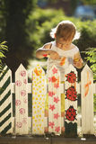Little girl paints fence. Little cute girl paints fence on summer Royalty Free Stock Photos