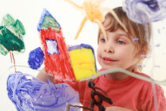 Little girl paints on glass, house, tree Royalty Free Stock Photo