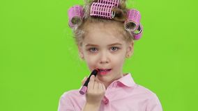 Little girl paints her lips with beautiful lipstick. Green screen. Slow motion stock footage