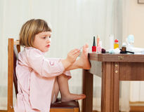 Little girl paints her nails Stock Photos