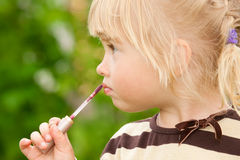 The little girl paints lips Stock Photography