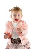 Little girl paints lips with lipstick Stock Images