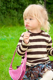 The little girl paints lips in park Royalty Free Stock Photo