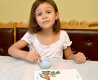 The little girl paints with paints a birds feeder Royalty Free Stock Images