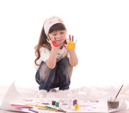 Little girl paints on a paper with paints Stock Images