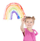 Little girl paints rainbow on window Stock Photography