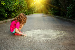 Little girl paints the sun on the asphalt in a sunset light. Royalty Free Stock Images