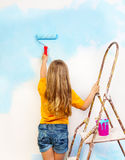 Little girl paints the wall standing on a ladder royalty free stock photos