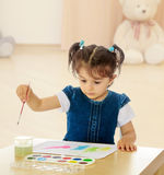 Little girl paints with watercolors at the table. Royalty Free Stock Photography