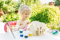 Little girl paints wooden model of house Stock Images