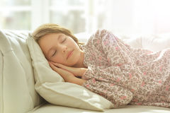 Little girl in pajama sleeping on couch. Cute little girl in colorful pajama sleeping on couch Royalty Free Stock Photo