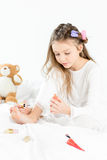 Little girl in pajamas and curlers applying nail polish to toenails Royalty Free Stock Photo