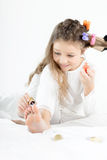 Little girl in pajamas and curlers applying nail polish to toenails Royalty Free Stock Images
