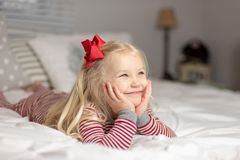 Little girl in pajamas laying on bed stock photo